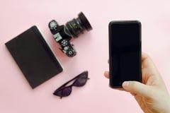 Übergeben Sie das Halten des stilvollen schwarzen Telefons und der Sonnenbrille, die Fotokamera Lizenzfreies Stockfoto
