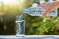 Übergeben Sie das Halten des strömenden Wassers der Trinkwasserflasche in Glas auf Holztisch stockfoto