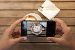übergeben Sie das Halten des Telefons, das Kaffeefoto auf Tabelle macht Stockfotografie