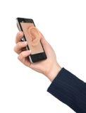 Übergeben Sie das Halten des Telefons mit dem Ohr auf dem Schirm Stockbilder