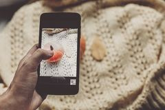 Übergeben Sie das Halten des Telefons und das Machen des Fotos des Kürbises und des Blattes auf warmem Lizenzfreies Stockbild