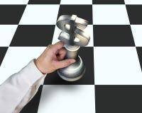 Übergeben Sie das Halten des USD-Symbolstückes, das Schach auf Tabelle spielt Lizenzfreies Stockbild