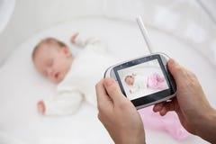 Übergeben Sie das Halten des Videobabymonitors für Sicherheit des Babys Stockbild