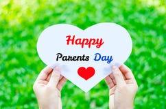 Übergeben Sie das Halten des weißen Herzpapiers mit glücklichem Elterntagestext Stockbilder