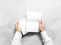 Übergeben Sie das Halten des weißen leeren Umschlags und beschriften Sie Modell, Stockbild