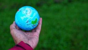 Übergeben Sie das Halten des Weltkugelballs mit Unschärfehintergrund Lizenzfreie Stockbilder