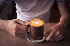 übergeben Sie das Halten einer Draufsichtoberflächenherzform des Tasse Kaffees im hölzernen Hintergrund Stockfotografie