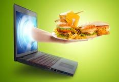 Übergeben Sie das Halten einer Platte des Lebensmittels aus einen Laptopschirm herauskommend Stockfotografie