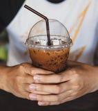 Übergeben Sie das Halten einer Schale kalten Kaffees, Milchtee, capucino Stockfotografie