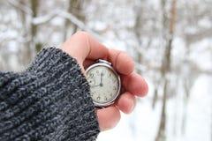 Übergeben Sie das Halten einer Taschenuhr, Winterzeitidee Stockbild