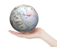 Übergeben Sie das Halten eines Balls gemacht von den verschiedenen Banknoten, lokalisiert Stockfotografie