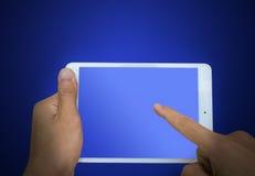 Übergeben Sie das Halten eines Berührungsflächen-PC, Noten mit einen Fingern der Schirm auf Blauem stockfoto