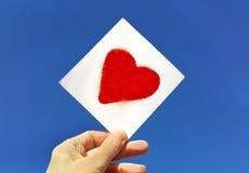 Übergeben Sie das Halten eines Bildes eines Herzens gegen den blauen Himmel Stockbild