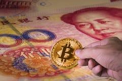 Übergeben Sie das Halten eines bitcoin und der Chinese Yuan-Rechnungen im Hintergrund Lizenzfreie Stockfotos