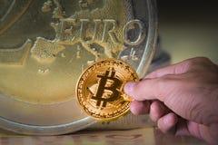 Übergeben Sie das Halten eines bitcoin und der Euromünzen im Hintergrund Lizenzfreie Stockfotos