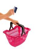 Übergeben Sie das Halten eines Einkaufskorbs und der Kreditkarte. Stockfotografie