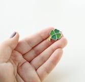 Übergeben Sie das Halten eines grünen Charmes des Kleeblattes Lizenzfreie Stockfotografie
