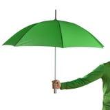 Hand, die einen grünen Regenschirm hält Lizenzfreie Stockbilder