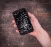 Übergeben Sie das Halten eines Handys mit einem defekten Schirm Stockfotos