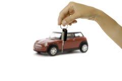 Übergeben Sie das Halten eines Schlüssels und des Autos am Hintergrund lizenzfreies stockfoto