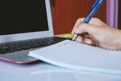 Übergeben Sie das Halten eines Stiftes, um auf Notizbuch zu schreiben und die Anwendung eines Computerlaptops für das Arbeiten lizenzfreie stockbilder