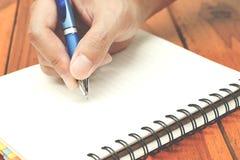 Übergeben Sie das Halten eines Stiftschreibens auf dem Notizbuch Lizenzfreies Stockbild