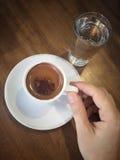 Übergeben Sie das Halten eines türkischen Kaffees der Schale auf Tabelle Stockfotografie
