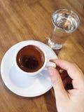 Übergeben Sie das Halten eines türkischen Kaffees der Schale auf Tabelle Stockbild