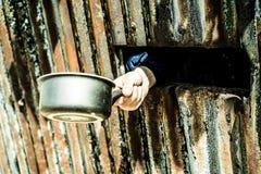 Übergeben Sie das Halten eines Topfes, Konzept des Welthungers Lizenzfreie Stockfotos