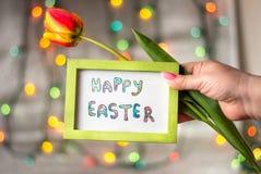Übergeben Sie das Halten glücklicher Ostern-Karte und der Tulpe Lizenzfreie Stockfotografie