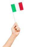 Übergeben Sie das Halten und das Hissen der kleinen italienischen Papierflagge Stockfotografie