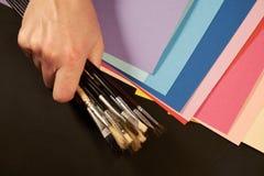 Übergeben Sie das Halten vieler Malereibürsten mit Mehrfarbenpapier Lizenzfreie Stockbilder