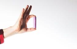 Übergeben Sie das Halten von AA, aaa, 18650 Batterien auf einem weißen Hintergrund Lizenzfreies Stockfoto