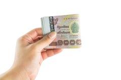 Übergeben Sie das Halten von den thailändischen Banknoten, lokalisiert auf weißem Hintergrund Stockbild