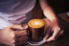 übergeben Sie das Halten von Draufsichtoberflächenherzform des Tasse Kaffees im hölzernen Hintergrund Stockbilder