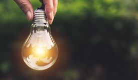 Übergeben Sie das Halten von Glühlampen mit dem Glühen auf Naturhintergrund Ideen-, Kreativitäts- und Einsparungsenergie mit Glüh stockfoto