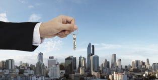 Übergeben Sie das Halten von Schlüsseln mit dem Bangkok-Stadthintergrund und nach Hause kaufen, den Immobilien und den Hausmietko stockfotografie
