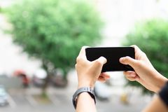 Übergeben Sie das Halten von Smartphone, von Bildgebrauch für bewegliche Anwendungen und von Multimediaprogrammen lizenzfreie stockfotografie