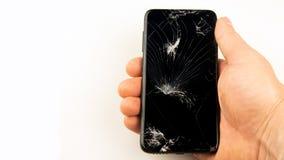 Übergeben Sie das Halten von Smartphone mit gebrochenem Schirm über weißem Hintergrund lizenzfreies stockfoto