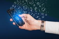 Übergeben Sie das Halten von Smartphone mit Hand gezeichneten Medienikonen und -symbolen Lizenzfreies Stockfoto
