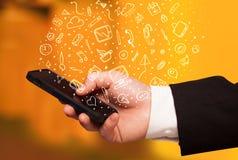 Übergeben Sie das Halten von Smartphone mit Hand gezeichneten Medienikonen und -symbolen Lizenzfreie Stockfotografie