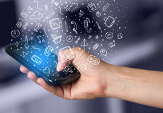 Übergeben Sie das Halten von Smartphone mit Hand gezeichneten Medienikonen und -symbolen Stockfotos