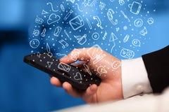 Übergeben Sie das Halten von Smartphone mit Hand gezeichneten Medienikonen und -symbolen Stockfoto
