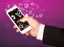 Übergeben Sie das Halten von Smartphone mit Medienikonen und -symbol Lizenzfreies Stockbild