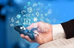 Übergeben Sie das Halten von Smartphone mit Medienikonen und -symbol Stockfoto