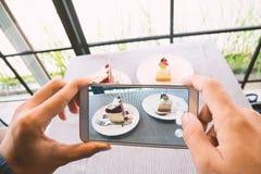 Übergeben Sie das Halten von Smartphone und das Machen des Fotos des Kuchens Stockbild