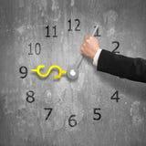 Übergeben Sie das Halten von Uhrhänden in der USD-Geldform auf alter Betonmauer Stockfoto