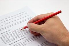 Übergeben Sie das Handeln des Korrekturlesens auf einem fehlerhaften Text mit rotem Stift Lizenzfreies Stockfoto