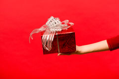 Übergeben Sie das Mädchen, das eine Geschenkbox auf rotem Hintergrund hält Lizenzfreies Stockfoto