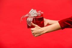 Übergeben Sie das Mädchen, das eine Geschenkbox auf rotem Hintergrund hält Stockbilder